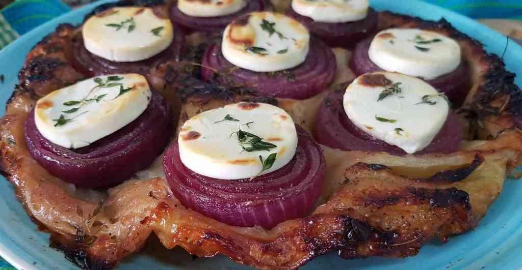 טארט טאטן של בצלים סגולים וגבינת עיזים, שנאפו מתחת לבצק מלאווח בזיגוג של בלסמי ותימין.