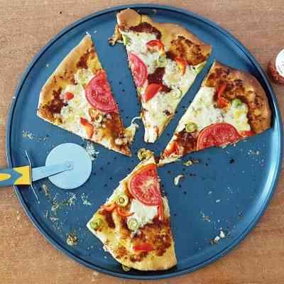 פיצה ברוטב עגבניות מיובשות עם פרמזן,עם תוספות של גבינה צהובה,זיתים וגמבה אדומה
